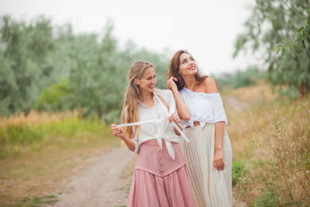 Two cheerful emotional best girlfriends in retro style clothes in retro clothes walk along the landing with the road on summer cloudy day. Walk together Reklamní fotografie