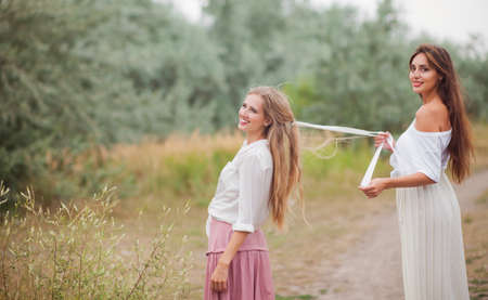 Two cheerful best girlfriends in retro-style clothes on landing with the road at summer day Reklamní fotografie