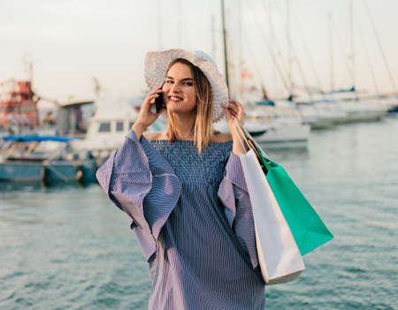 Portrait of a cheerful young shopaholic woman in a hat and dress on a background of the sea. Happy shopping concept. Stock Photo