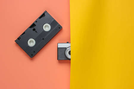 Retro objects. Half film camera, video cassette on pink-yellow background. 80s. Top view