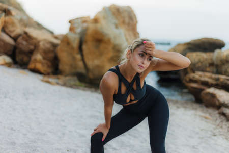 Tired attractive fitness woman in sportswear on a wild beach.