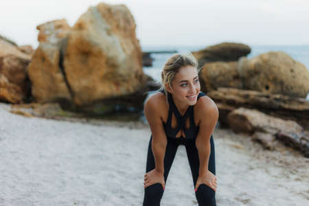 Tired attractive fitness woman in sportswear on a wild beach. Banco de Imagens