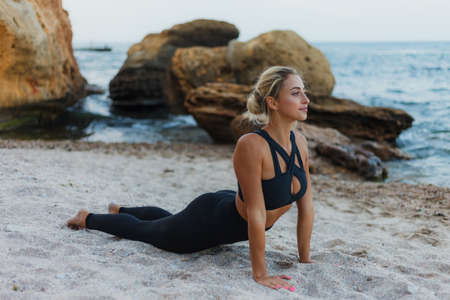 Young pretty sport woman in sportswear practicing asana exercise on the sand at the wild beach. Outdoor yoga training