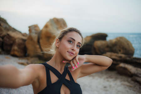 Selfie portrait of young attractive blonde woman in swimsuit at wild beach