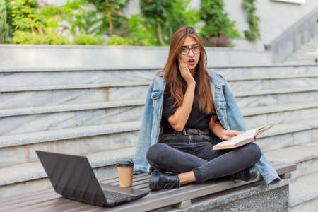 Modern students. Distance learning. Young enthusiastic woman reads book while sitting on bench with a laptop Foto de archivo
