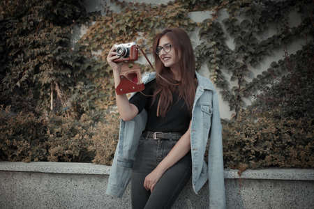 Young hipster woman in denim jacket and glasses enjoys film retro camera outdoors