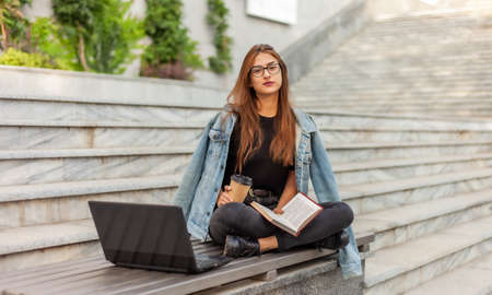 Modern students. Distance learning. Young hipster girl reads book while sitting on bench with a laptop Banco de Imagens