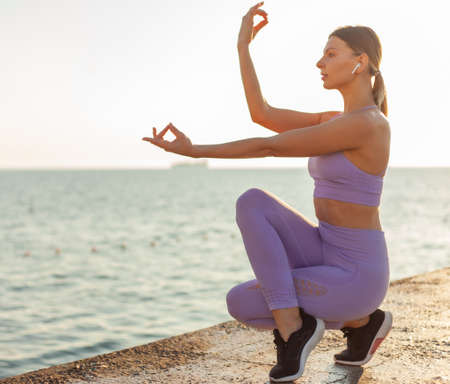 Young slim woman practicing yoga. Meditation at sunrise. Healthy lifestyle concept, balance Banco de Imagens