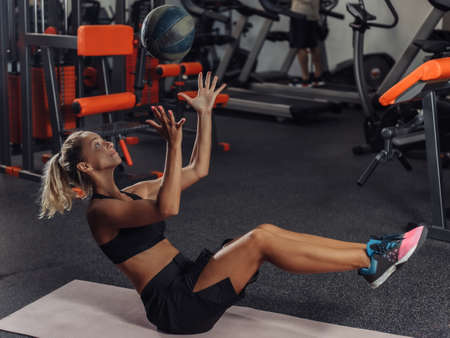Young attractive sport woman in sportswear training with medicine ball in the gym. Functional Training Concept