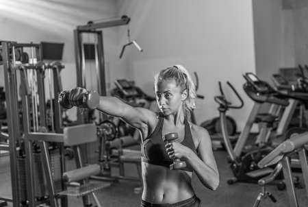 Fit woman in sportswear practicing hand punch with dumbbells at gym. Banco de Imagens