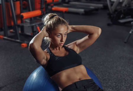 Young slim woman in sportswear is training abdominal muscles on fit ball in gym