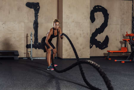 Young sport woman in sportswear is training with battle rope in the gym. Functional training. Healthy lifestyle concept