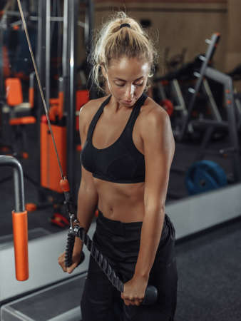 Sportswoman in sportswear trains triceps in exercise machine in the gym Banco de Imagens