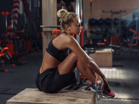 Young attractive sport woman in sportswear resting between sets at workout in the gym