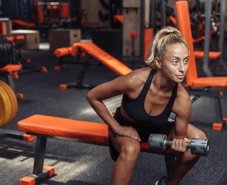 Young fitness woman doing concentrated doing dumbbell lifts for biceps one hand while sitting on a bench in the gym. Training concept with free weights.