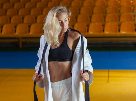 Young judoka woman in white kimono and black belt posing in the sports hall Banco de Imagens