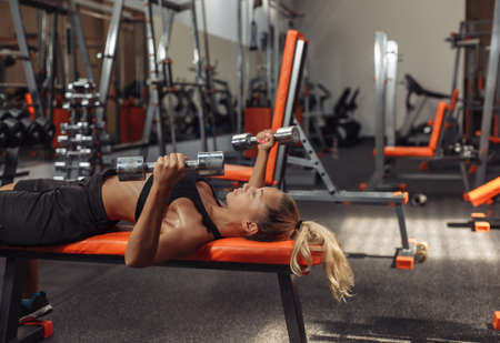 Slim fit woman in sportswear is practicing bench press with dumbbells while lying on a bench in the gym. Training concept with free weights. Functional training