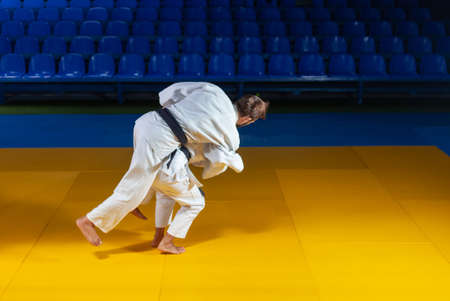 Martial arts. Sparing Portners. Sport man and woman in white kimono train judo throws and captures in the sports hall Banco de Imagens