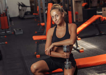 Fitness woman in sportswear sitting on a bench with dumbbell and resting in the break between sets of exercises in the gym