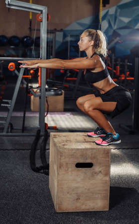 Young attractive sport woman in sportswear is practicing jumping on a wooden box in the gym. Functional Training Concept Banco de Imagens