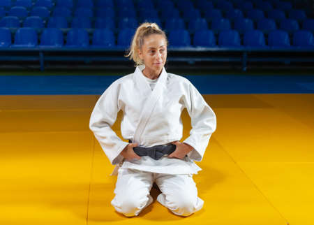 Young judoka woman in a white kimono with a black belt sits on the floor in the sports hall Banco de Imagens