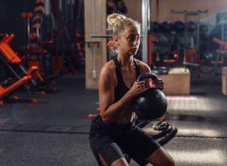 Young fit woman in sportswear doing exercise with kettlebell in the gym. Healthy lifestyle concept. Body training with free weights. Functional training