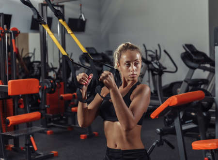 Young attractive sport woman in sportswear is training with fitness straps in the gym. Functional Training Concept Banco de Imagens