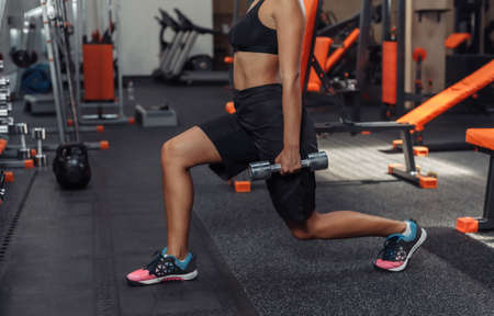 Slim fit woman in sportswear practicing lunges with dumbbells in her hands in the gym. Training concept with free weights. Functional training Banco de Imagens