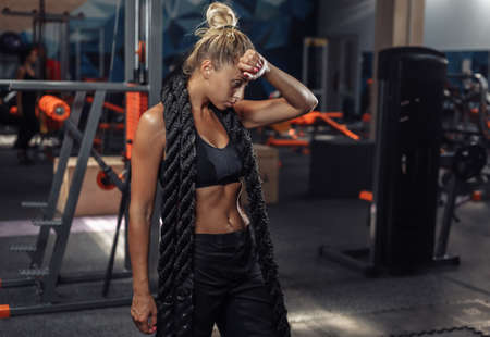 Tired sport woman in sportswear with battle rope on her neck in the gym. Functional training. Healthy lifestyle concept Banco de Imagens