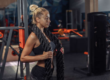 Young sport woman in sportswear with battle rope on her neck in the gym. Functional training. Healthy lifestyle concept Banco de Imagens