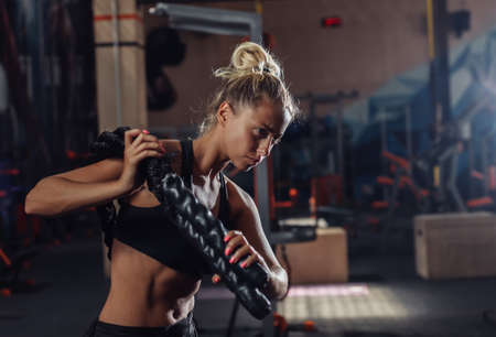 Young sport woman in sportswear is training with battle rope on her shoulders in the gym. Functional training. Healthy lifestyle concept
