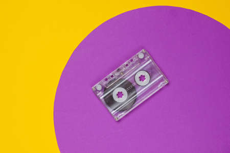 Audio cassette on yellow background with purple circle. Studio fashion shot. 80s, pop culture. Top view.
