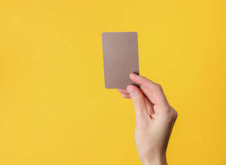Female hand holds a blank brown business card on yellow background