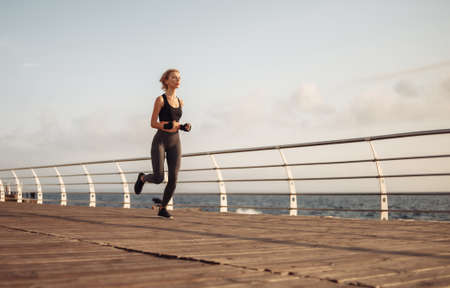 Morning run. Young athletic woman in sportswear runs on the beach at sunrise. Outdoor workout. Healthy lifestyle Stock fotó