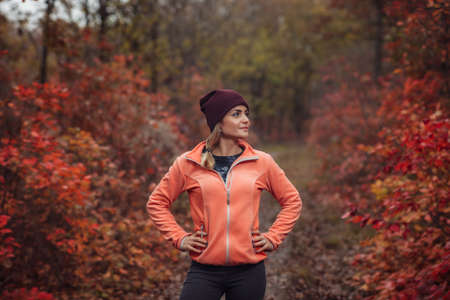Image of a young fit woman in sportswear in the autumn forest with reddened leaves on the trees
