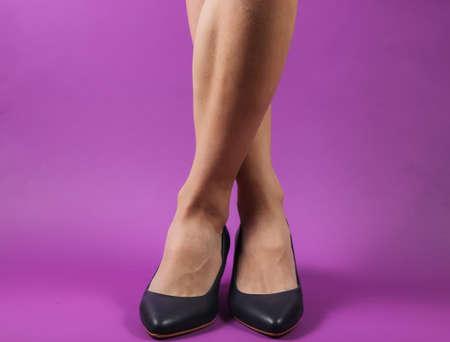 Slim female legs with classic high heel shoes on purple background. Studio fashion shot