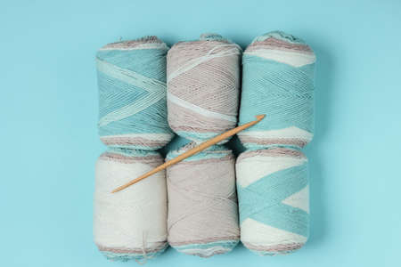 Woolen skeins of thread and crochet hook on blue background. Top view