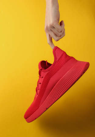 The hand holds red sports shoe on yellow background. Studio shot