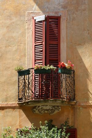 Detail of a window in a colorful wall, warm Italian sunlight and the real mediterranean atmosphere Archivio Fotografico