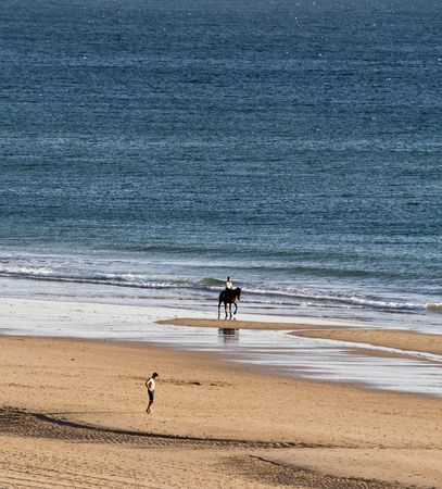 wavily: Horsewoman and Jogger at the beach in Andalusien Stock Photo