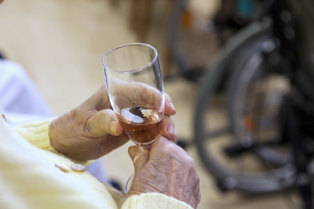 old senior citizen holding a glass of champagne in their hands Standard-Bild