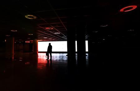 leer: Mann laeuft allein durch eine unterirdische Halle in Richtung Notausgang