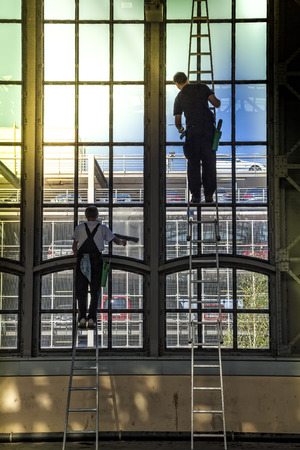 Two men cleaning the windows of an industrial plant 스톡 콘텐츠