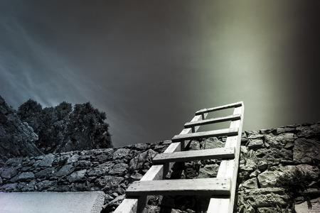 Houten ladder leunend tegen een vestingmuur Stockfoto