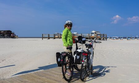 reisen: woman when with bike tour on the beach of the North Sea Stock Photo