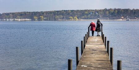 eventide: Two senior women on a pier at wannsee in berlin