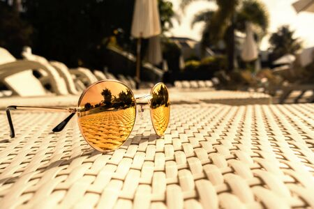 Sunglasses are lying on a sun lounger by the pool
