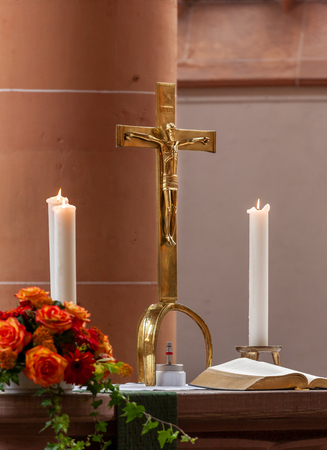 cross of Jesus and candles at an altar in a catholic church