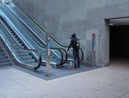 A man with complete scuba gear is standing at an escalator at Berlin Central Station Imagens