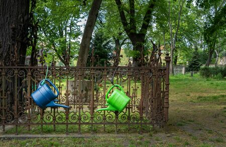 Watering cans hang on a rusty fence in the cemetery Banco de Imagens